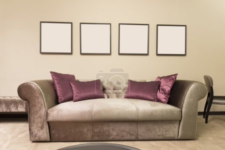 Photo for Sofa in a room with four empty picture frames - Royalty Free Image