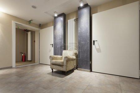 Photo pour Fauteuil dans le couloir de l'hôtel - image libre de droit