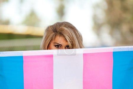 Hispanic Transgender hiding face with pride flag
