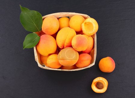 Apricots. Group of harvested apricots on a basket, top view, Blackboard background.