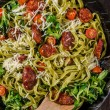 Pasta salad with sausage, topped with parmesan che...