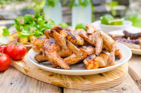 Outdoor barbecue, chicken wings, fried sausage and...