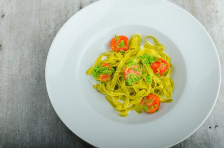 Pasta with basil pesto and pine nuts, cherry tomatoes