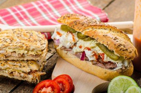 Photo pour Sandwich au porc panini, long porc cuit au four, baquette fraîche avec salade fraîche et saucisse chaude - image libre de droit