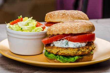 Photo for Vegetarian chickpea burger, tomato and dip of herbs, garlic and yogurt and salad with cherry tomatoes - Royalty Free Image