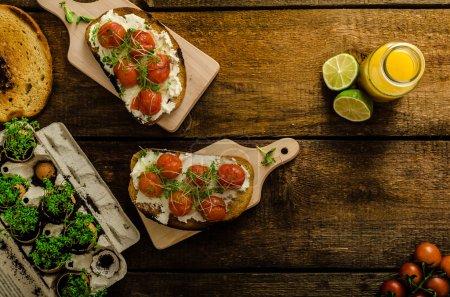 Photo pour Rôti Sauce tomate cerise et Ricotta sur Toast, jus d'orange pressé frais au citron vert, ail bio et micropousses sur tomate, cuit au thym - image libre de droit