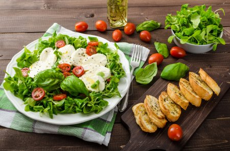Photo for Lamb's lettuce salad with mozzarella, tomato and basil, topped with olive oil and herbs - Royalty Free Image