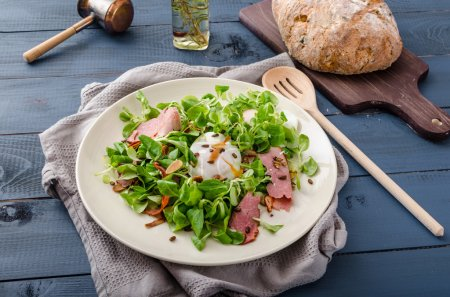 Photo for Lamb's lettuce salad with roasted nuts, smoked rump and poached egg, rustic italian bread with olives - Royalty Free Image