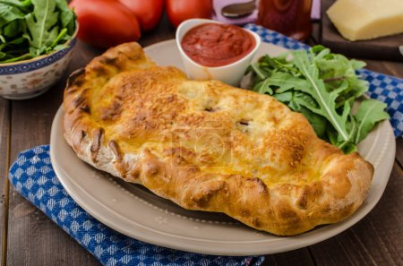 Calzone pizza stuffed with cheese and prosciutto