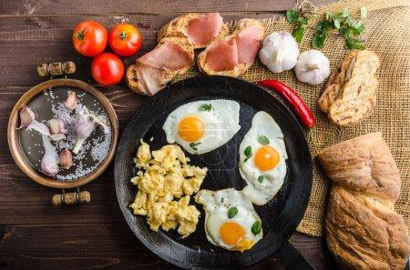 Photo pour Petit déjeuner protéiné complet - pain grillé à l'ail avec œufs et muffins, tomates cerises, jambon italien sec - image libre de droit