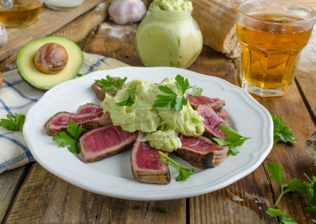 Beef steak with avocado dip and herbs