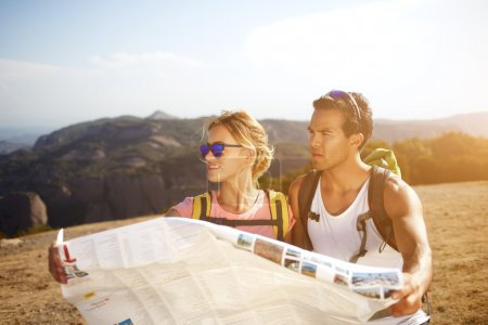 Male and female backpackers are looking for a new way to continue their hike in rural during summer trip