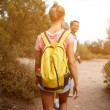 Back view of a young two travelers are walking in ...