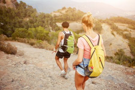 Two hikers with rucksacks on backs are exploring new places during their long awaiting amazing travel