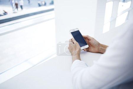 Photo pour Femme d'affaires tenant un téléphone portable. Femme gestionnaire lit les nouvelles financières sur Internet via téléphone mobile pendant la pause de travail - image libre de droit