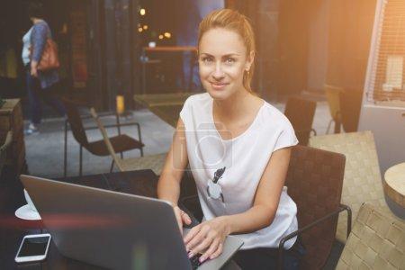 Foto de Retrato de una dama hermosa, sentado en la mesa de café de acera con ordenador portátil abierto, joven encantadora mujer posando durante el trabajo en su portátil net-book pretty caucásica mujer utilizando la tecnología - Imagen libre de derechos