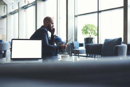 Photo pour Homme entrepreneur regardant sur pavé tactile un mauvais chiffre de revenu le mois dernier et écoutant téléphone mobile à l'explication du subordonné, tout en étant assis près du net-book avec écran d'espace de copie - image libre de droit