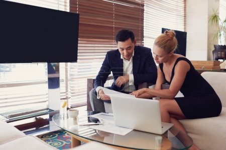 Young man and woman skilled CEOs  while are sitting in informal atmosphere near screen with copy space