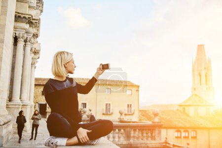 Gorgeous female tourist is shooting video of beautiful city landscape on her cell telephone