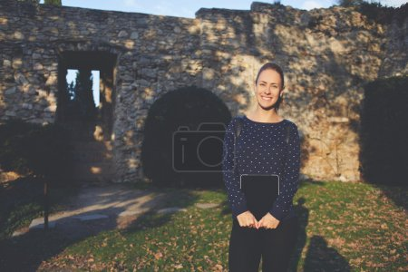 Photo for Young female student with wonderful smile on her face is holding portable touch pad while standing at university campus. - Royalty Free Image