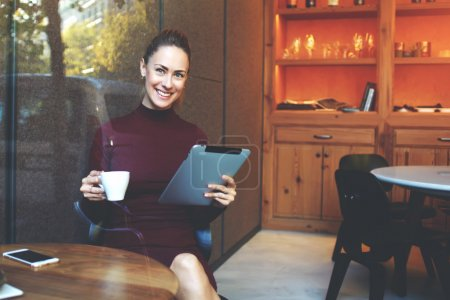 Attractive female freelancer holding touch pad and smiling for the camera while resting in cozy cafe