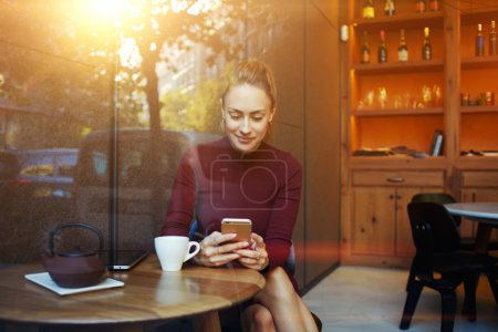 Charming happy female reading fashion news on cell telephone during breakfast in restaurant