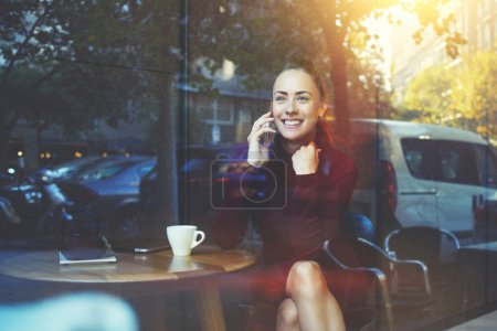 Young cheerful female calling with cell telephone while sitting in coffee shop
