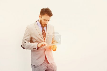 Male manager is using digital tablet, while is standing near copy space for your advertise text message