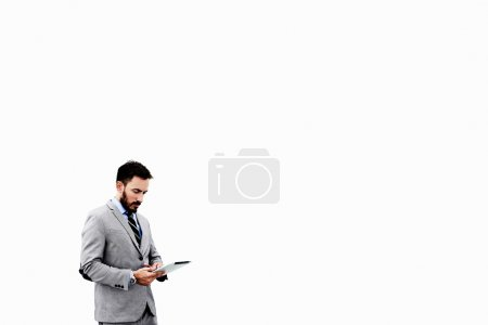 Young CEO is reading news on web page via portable...
