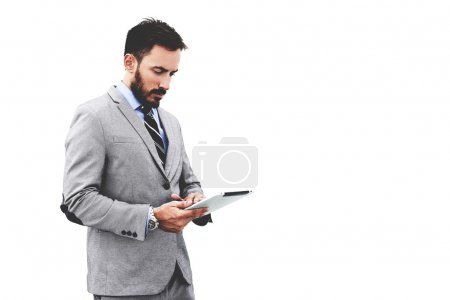 Young handsome male with touch pad in hands is standing in modern interior