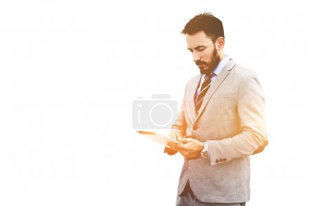 Photo for Male professional banker is reading information on Foreign Exchange via digital tablet,while is standing against white wall background with copy space for advertise text message or promotional content - Royalty Free Image