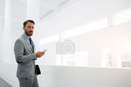 Photo for Young man skilled office worker is holding mobile phone and looking at camera, while is standing in hallway company near copy space. - Royalty Free Image