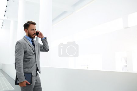 Photo for Young man professional banker with digital tablet in hand is talking on smart phone during work break - Royalty Free Image