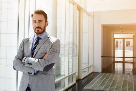 Photo pour Homme d'affaires réussi habillé en costume coûteux est debout dans le couloir de son entreprise près de l'espace de copie pour votre message texte publicitaire ou contenu promotionnel . - image libre de droit