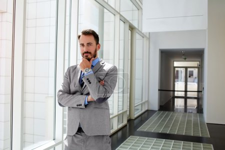 Male serious government worker in luxury suit is standing in modern interior before conference