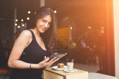 Modern business woman with digital tablet in hands is sitting in modern coffee shop interior.