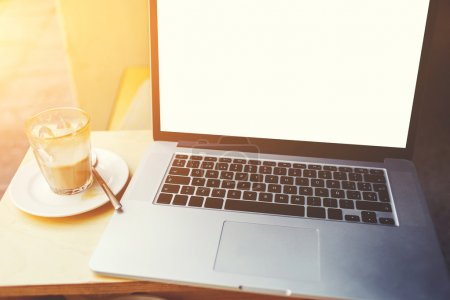 Laptop computer lying near cup of coffee on wooden table in sidewalk cafe