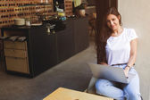 Gorgeous female freelancer using net-book for distance job while sitting in modern coffee shop