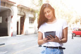 Portrait of a stylish hipster girl is using digital tablet for navigation in urban setting