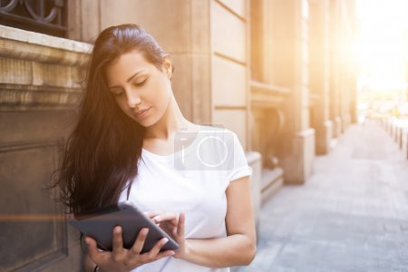 Gorgeous female tourist using touch pad for navigation in city during vacations abroad