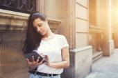 Beautiful hipster girl is using on touch pad in urban setting