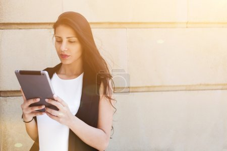 Photo for Latin businesswoman is using digital tablet computer while is standing against street wall background with copy space area for text message or content - Royalty Free Image