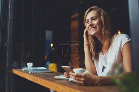 Photo pour Heureuse femme utilisant un téléphone intelligent tout en se relaxant dans un café après avoir marché pendant son week-end d'été - image libre de droit
