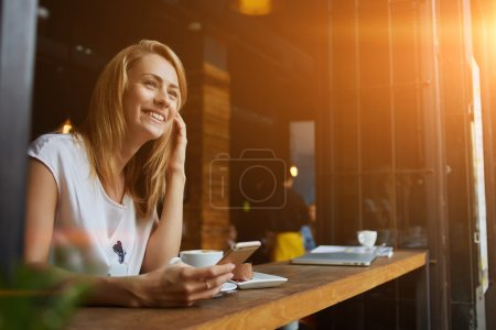 Charming smiling hipster girl received good news on cell telephone while she sitting in cozy coffee shop