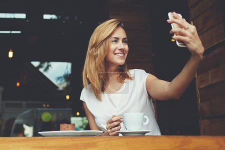 Cheerful woman posing while photographing herself for social network picture, copy space