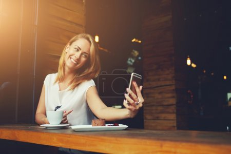 Pretty woman with cute smile making self photo on her smart phone during rest in cafe