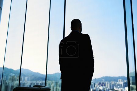 Silhouette of a successful businessman in suit is thinking about future of his company