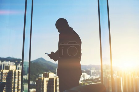Male emploee with cell telephone in hands is standing in office near big skyscraper window with city view