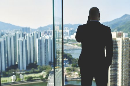 Young male lawyer is calling with cell telephone,  while is standing near office window with view of tall skyscrapers
