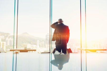 Photo pour Homme PDG est debout dans l'intérieur du café moderne contre la fenêtre avec un fond d'espace de copie pour votre message texte - image libre de droit